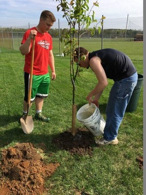 Kyle and Austin water a tree at The Giving Garden at Northland Lutheran High School in Kronenwetter.