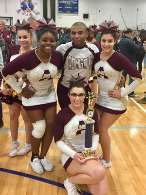 Arlington cheerleaders AJ Pittore, Za'ire People, Will Adams, Arianna Racano flank Rachel Prandoni as she kneels with a trophy Saturday.