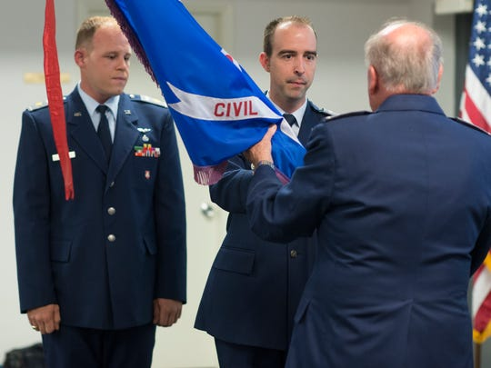 Maj. Dirk DeVille, center, hands the Civil Air Patrol flag to Lt. Col. Jim Kaletta, the deputy commander of CAP Group 5, as Maj. Kevin Dinger Jr. looks on during a change of command ceremony at the Naples Civil Air Patrol Monday night, Aug. 22, 2016. DeVille is the outgoing commander of the Naples Cadet Squadron of the Civil Air Patrol, and Dinger  is the new commander.
