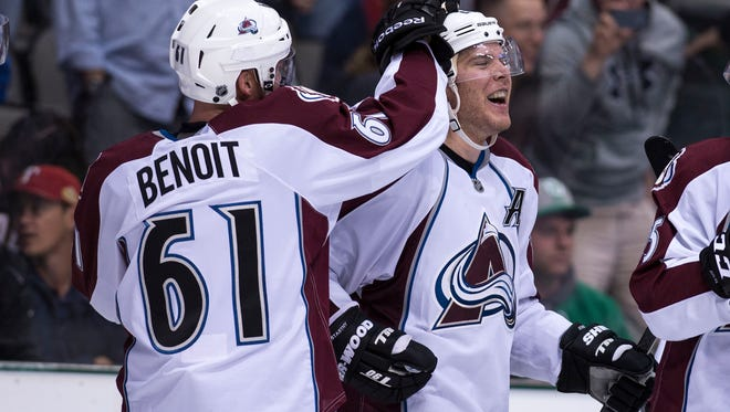 Avalanche center Paul Stastny, right, and defenseman Andre Benoit celebrate the game-winning goal against the Stars at American Airlines Center.