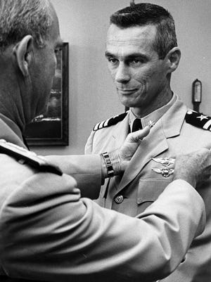 Eugene A. Cernan (right),  a former commander in the U.S. Navy and Gemini Nine astronaut, received his astronaut wings from Chief of Naval Operations Adm. David L. McDonald (left) during a ceremony in the Pentagon July 26, 1966. Cernan served 20 years in the United States Navy as an aviator and later as an astronaut through the NASA space program.
