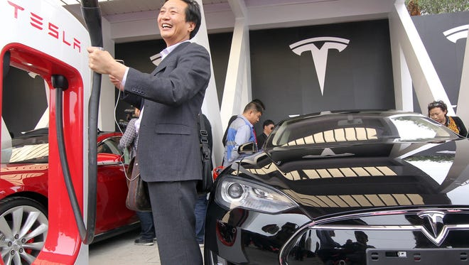 "A Chinese guest poses for a photo by a Tesla ""supercharger"" on a car handover ceremony in Shanghai as American electric carmaker Tesla Motors delivers their Model S cars to its first buyers in China in April"
