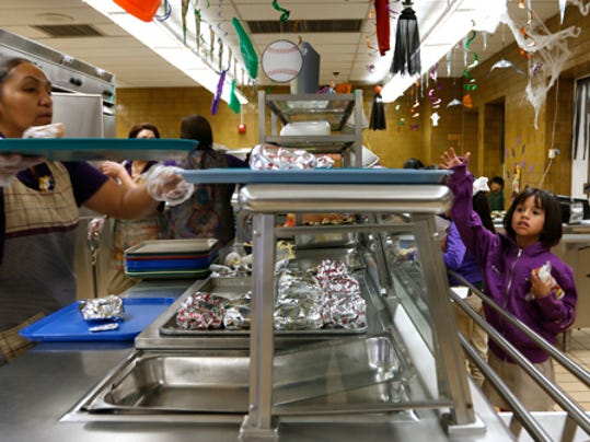 Cafeteria workers at Douglass Elementary School in south El Paso hand out food to students during the lunch break.