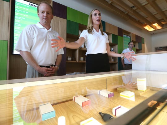 Trulieve CEO Kim Rivers and COO Jason Pernell stand behind the counter Tuesday at the company's dispensary, the first to open in the state of Florida.