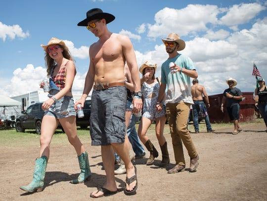 Festival-goers walk through campgrounds during Day