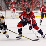 Washington Capitals center Evgeny Kuznetsov (92) and Boston Bruins center Patrice Bergeron (37) battle for the puck in the third period at Verizon Center. The Capitals won 3-0.