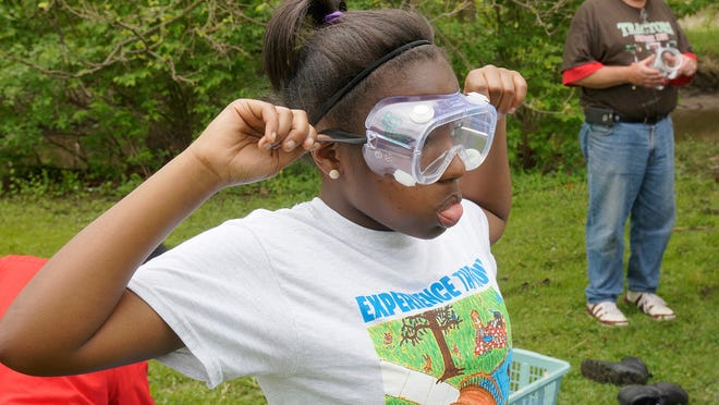 LaKyla Mullins wears protective goggles for handling the samples of river mud.