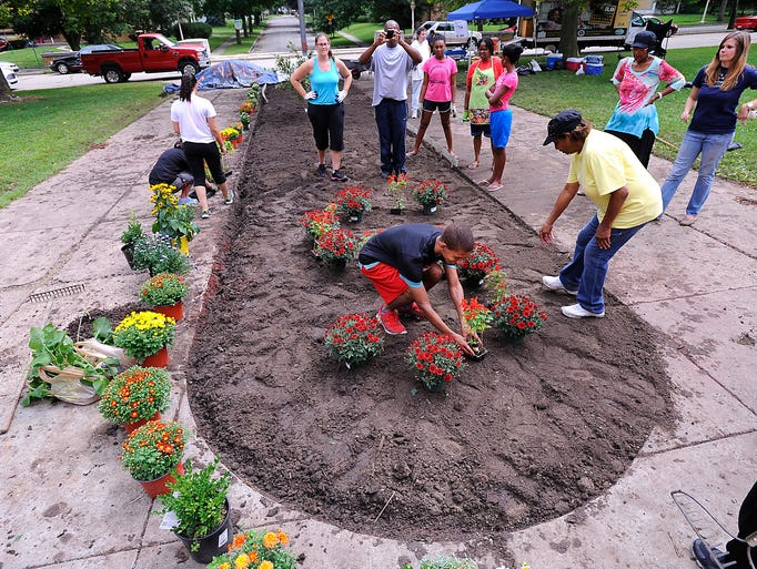 """The """"S"""" for Sexton High Schoo is laid out in flowering plants  as  students, football team members  and community  supporters  all  worked  on a school beautification project at the Lansing School Friday morning . Picture taken Friday  8/22/2014."""