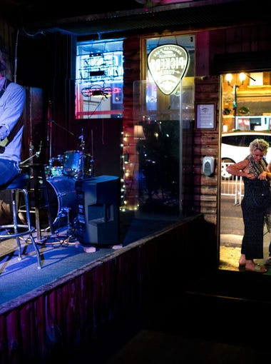 Alex Hernandez, who performs under the name Rocky Bottom, plays a set as guests enter the front door at Bootleggers Inn, Tuesday, May 22, 2018, in Nashville, Tenn.
