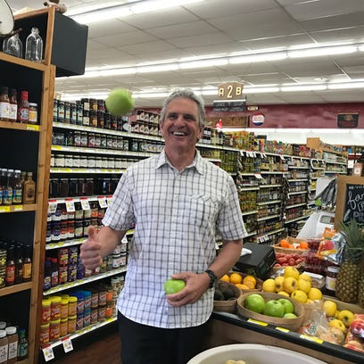 David Apple, the owner of Apple Market, juggles a couple