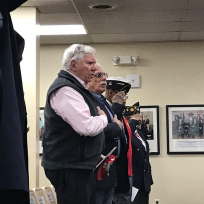 Military veterans stand in salute during Montclair's