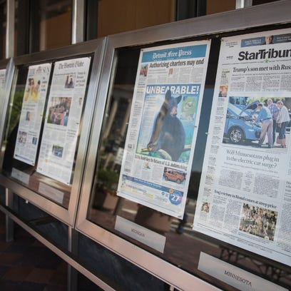 Newspaper front pages are displayed at the Newseum