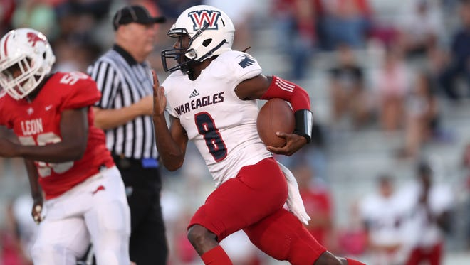 Wakulla's Jaylon Worsham scrambles out of the pocket during their game against Leon at Cox Stadium on Thursday night.