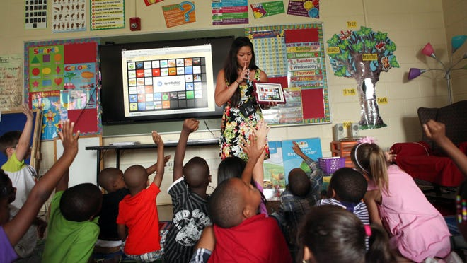 Kindergarden teacher Regina Becker leads her class lesson with the use of an iPad linked to a nearby 70 inch television with Apple TV, at New Castle Elementary School.