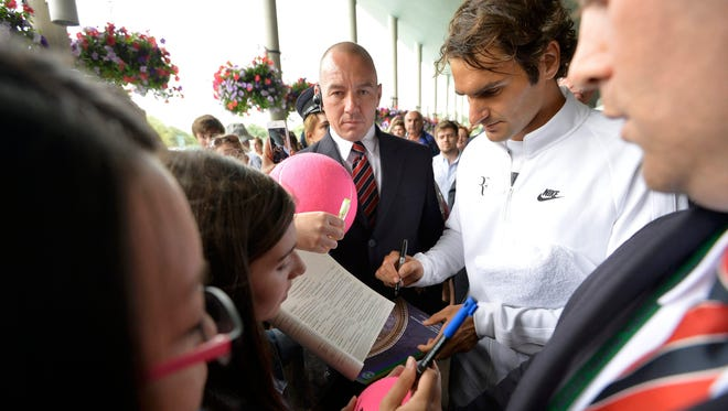 Roger Federer signs autographs Saturday following a practice session at Wimbledon in London.