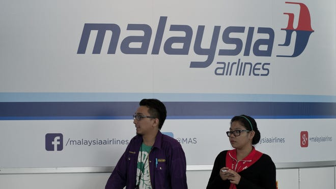 Visitors walks past the Malaysia Airlines logo at Kuala Lumpur International Airport (KLIA) in Sepang, outside Kuala Lumpur on March 16, 2014.