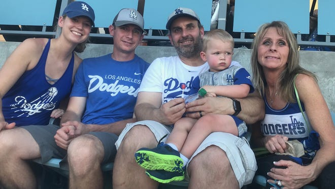 Aaron Johnson holds grandson Joc as Jolyn Johnson (far left), Levi Johnson (second from left) and his mom Stephanie (far right) attend Game 1 of the World Series last week in Los Angeles.
