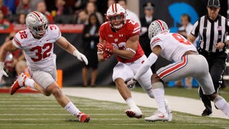 Wisconsin running back Jonathan Taylor puts a move on Ohio State  cornerback Kendall Sheffield during the 2017 Big Ten championship game.
