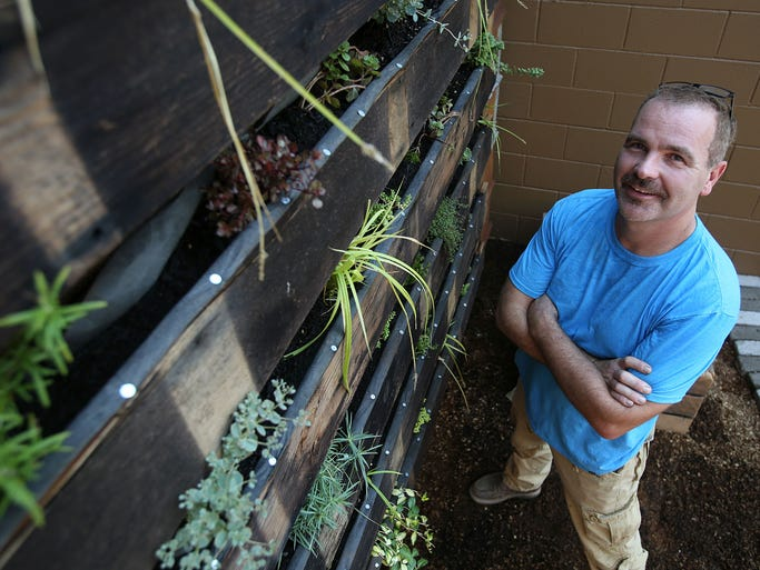 Bruce Wadleigh, owner of Barnwood Naturals, transformed a wall of his business, at the base of the Union St. pedestrian bridge, into a â??living wallâ? using recycled lumber and donated native plants. Wadleigh poses for a photo on Monday, Aug. 11, 2014 in Salem, Ore.