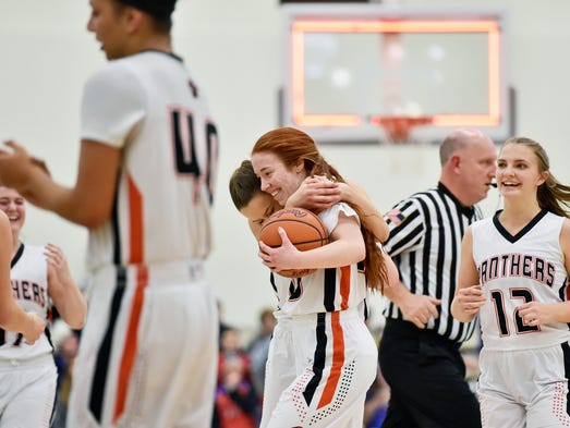 Central York's Emma Saxton is hugged by teammate Megan