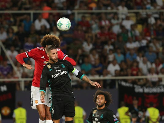 Manchester United's Marouane Fellaini ,and Real Madrid's Sergio Ramos, front, challenge for a header during the UEFA Super Cup final soccer match between Real Madrid and Manchester United at Philip II Arena in Skopje, Tuesday, Aug. 8, 2017. (AP Photo/Boris Grdanoski)