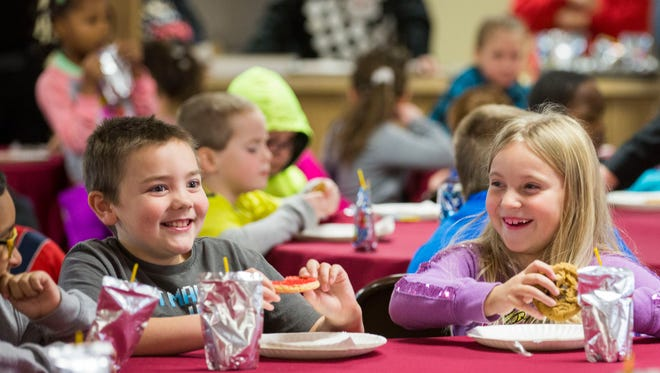 Jake Carson, 8, and Iris Tanner, 7, laugh as they eat their cookies before receiving presents at the annual Christmas party put on by the Evansville FOP on Saturday morning.