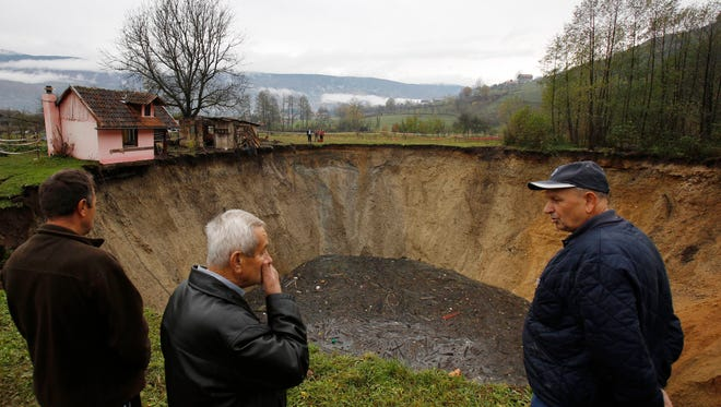 People gather around a huge sinkhole in the village of Sanica, Bosnia, on Nov. 21.