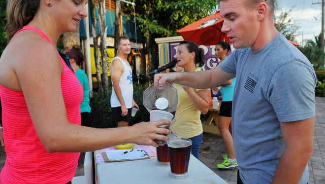 Caittin Loughran of Melbourne gets a beer from Cody Long of Rockledge after Tuesday nights Running for Brews weekly event held at the Satellite Beach Long Doggers on South Patrick Dr. Around one hundred participants came out for the run.