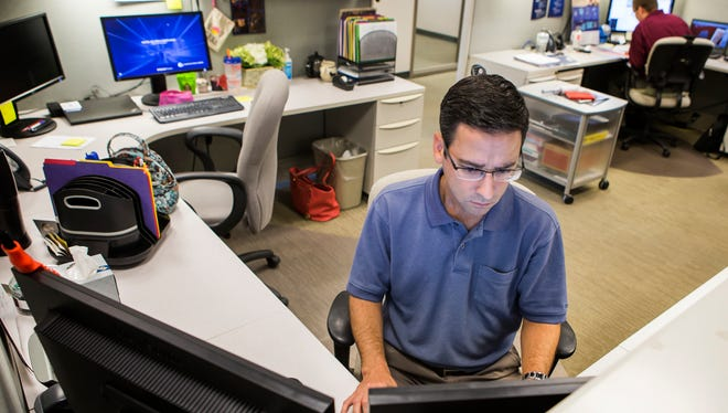 Rob Kalesse works at his desk at Corporation Service Company's Centerville Road office in this August 2016 photo.
