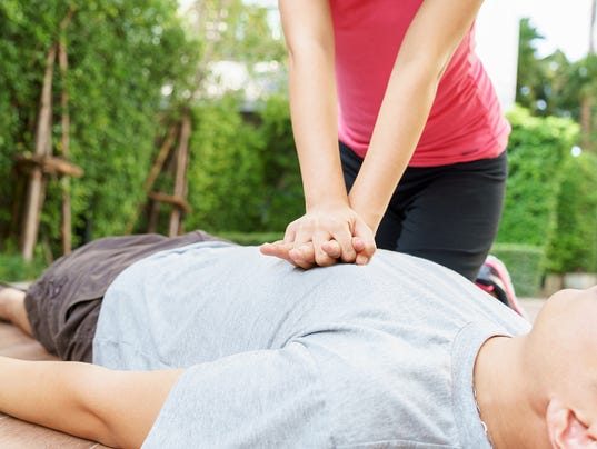 Woman giving cardiopulmonary resuscitation (CPR) to a man at public park.