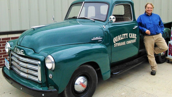 Antique Chevy trucks like this one are a focal point of the Quality Care Storage Company branding image.  Founder and owner Dean Moore rests against one at his North Liberty site.