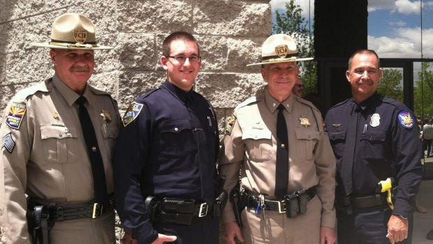 Flagstaff Police Officer Tyler Stewart stands between his father Sgt. Frank Stewart, left, and his grandfather Lt. Col. Jeff Raynor, right, both Arizona Department of Public Safety Officers and his uncle Officer Tim Stewart who is with the Phoenix police department at his graduation from the police academy.