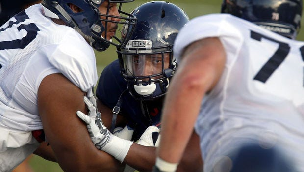Defensive lineman Reggie Gilbert looks into the backfield while dueling with teammate Freddie Tagaloa on a snap.