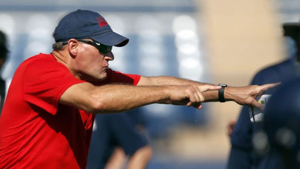 Head coach Rich Rodriguez declares a winner as the offensive players go one-on-one against defensive players during a drill for the University of Arizona football team.