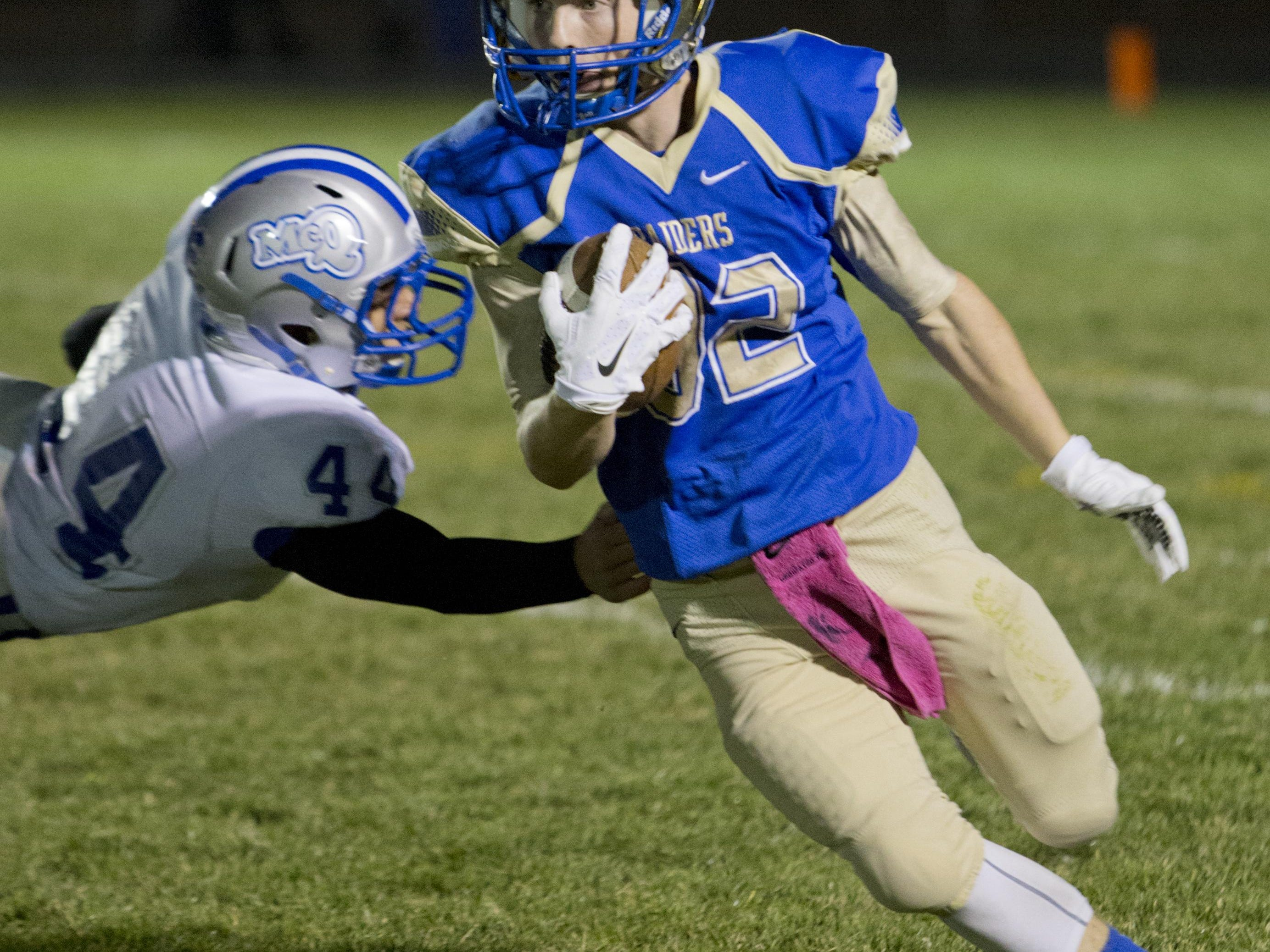 Reed's Robert Ferrel breaks a tackle against McQueen on Friday.