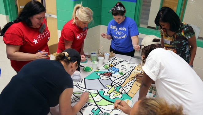 Clockwise from bottom left: Nancy Colyar, Stephanie Carreras, Renata Twadell, Kristina Danko, Vicki Yates, Tuwanda Coleman and Lourdes Sosa volunteer with Hands On Nashville to work on a painting that will be on display at J.E. Moss Elementary School encouraging children to make healthy food choices.