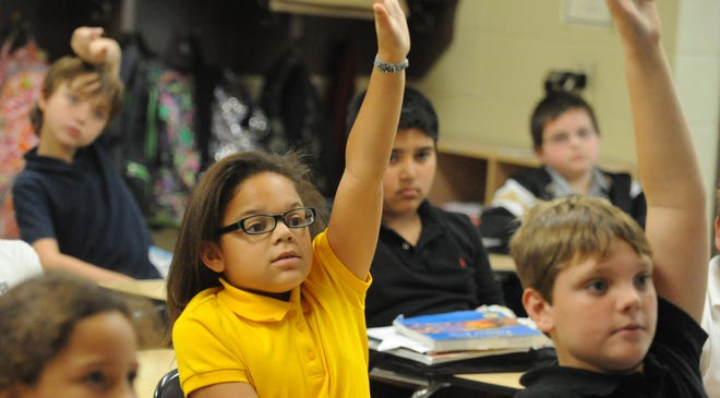 Oak Grove Upper Elementary fourth-graders raise their hands to answer questions during Language Arts class.
