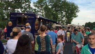 Customers lined up outside Dallas Shaw's Hoss' Loaded Burgers food truck along side other mobile food vendors.