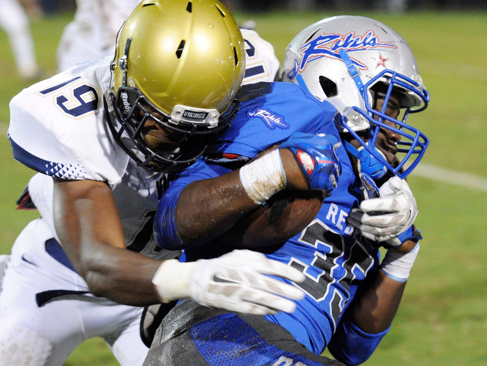 Byrnes running back Quez Mayes (35) is stopped by Spartanburg's Mike Murphy (19).