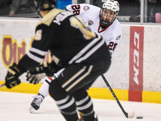 St. Cloud State's Kevin Fitzgerald passes around Western Michigan's Scott Moldenhauer during the first period Friday, Jan. 12, at the Herb Brooks National Hockey Center.