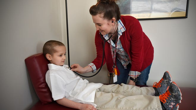 STRIDE Academy nurse Kelly Meyer checks on student Vincent Westlund at the school. STRIDE is one of about 100 schools nationwide participating in a program that utilizes app-enabled thermometers.