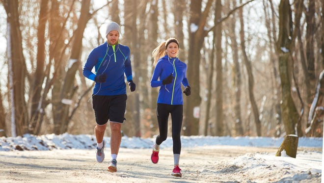 Young couple in the winter running together in nature
