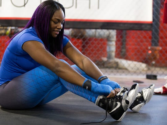 Claressa Shields ties her shoes before practice on