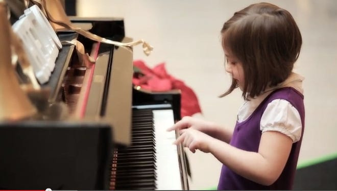 """A debate is going on on whether a viral video featuring this little girl playing """"Chopsticks"""" is real or fake."""