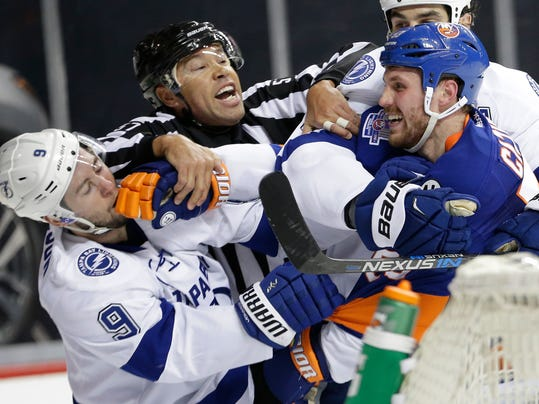 "FILE - In this May 3, 2016, file photo, linesman Jay Sharrers, center, tries to break up a fight between Tampa Bay Lightning center Tyler Johnson (9) and New York Islanders center Casey Cizikas (53) during the first period of Game 3 of the NHL hockey Stanley Cup Eastern Conference semifinals in New York. Even though Shandor Alphonso never envisioned his hockey career taking him to officiating, he didn't have to look far to see it was possible. As a young, black player, all Alphonso had to do was watch ""Hockey Night in Canada"" or the Stanley Cup Final and he saw fellow minority Jay Sharrers working as a linesman. (AP Photo/Frank Franklin II, File)"