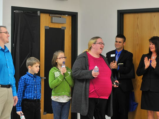 Buska Retirement Solutions president Suzanne Buska, right, and staff Brian Gaunt, give an applause to Amanda Witter, her 10-year-old daughter Melodie, 7-year-old son Aissen, and husband Michael Friday afternoon in a community room at the Village of Rothschild.