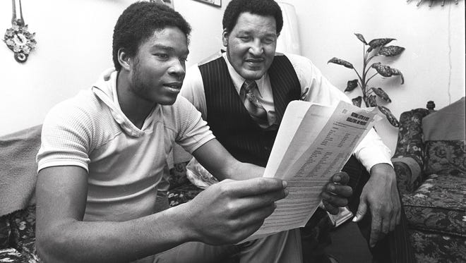 Bolton High School's Otis Jackson, left, and Bolton coach Joe Branch look over the paperwork that will make Jackson a Memphis State Tiger in April 1978. Jackson, a 6-1 All-State guard, led Bolton to the state Class A Championship and was voted the most valuable player in the class A state tournament. He led Bolton to 70 victories over the past two seasons.