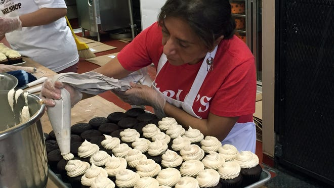 Celia Concepcion, who owns bakeries in El Salvador, ices cupcakes at Carlo's Bakery in Hoboken, New Jersey.