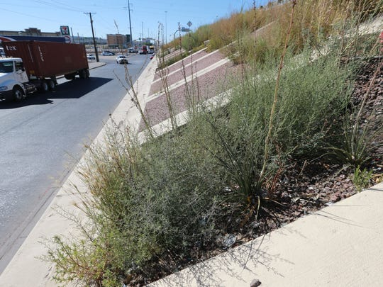 Weeds and other vegetation grow in the retainer walls of Interstate 10 near Zaragoza Road. The truck at left is traveling west on Gateway West Boulevard.