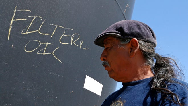 """In this Aug. 18, 2015 photo, Joe Ben Jr., Shiprock Chapter House Farm Board representative, points to an area on the water where it states """"filtered oil"""" in Shiprock, N.M. The quality of San Juan River water on the Navajo Nation has returned to what it was before a spill at a Colorado gold mine sent toxic sludge into the waterway, federal officials said Thursday."""